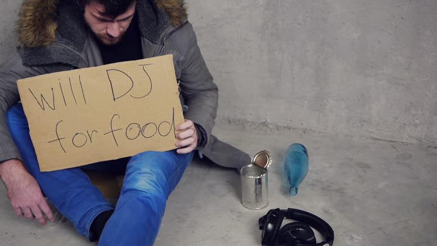 homeless dj sitting on the floor upset