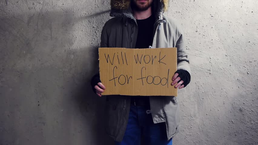homeless man standing at the wall with a cardboard