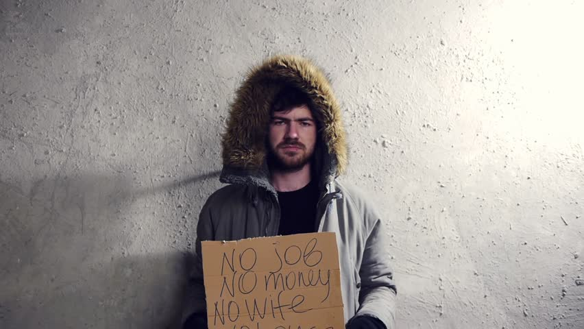 homeless man standing at the wall and asking for help