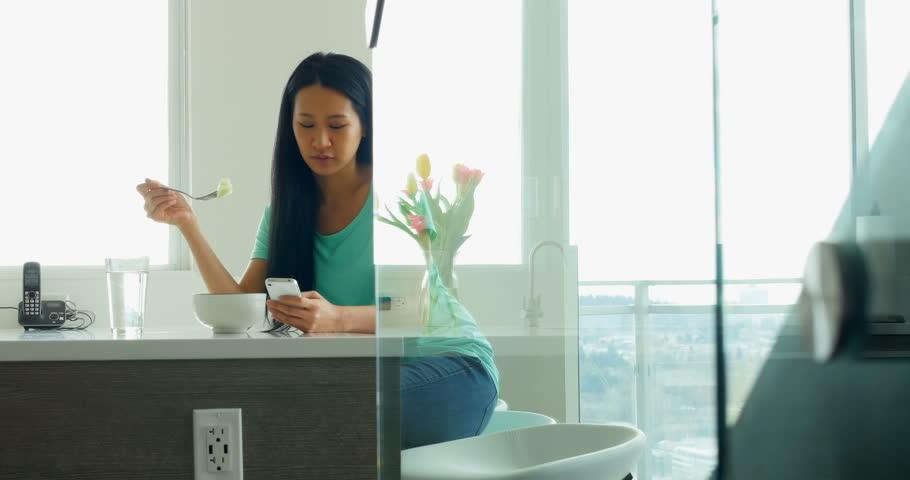 Woman using mobile phone while having breakfast in kitchen 4k | Shutterstock HD Video #33243490