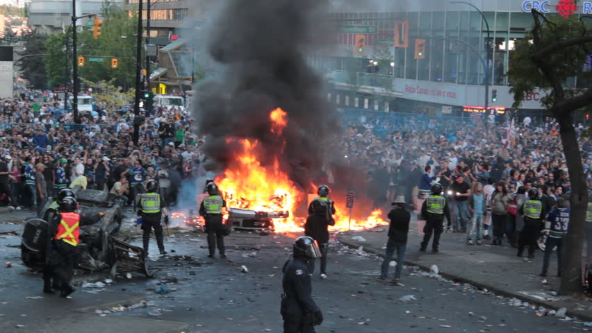 VANCOUVER, CANADA - JUNE 15 Police and crowd yelling as car burns during the 2011 Vancouver Stanley Cup riot on June 15, 2011. The 2011 Vancouver Stanley Cup riot was a public disturbance that broke out in downtown Vancouver, BC, Canada on Wed, June 15, 2