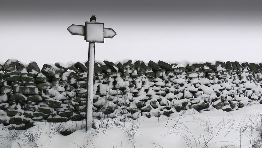 Winter Sign Post. A sign post covered in snow in front of a Drystone wall.