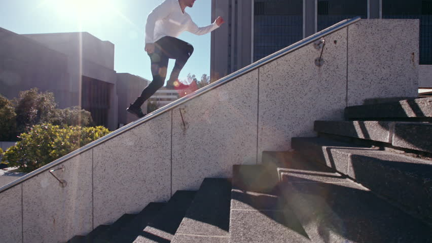 Young urban man doing parkour tricking and freerunning in the city. Young man practicing extreme sport outdoors, jumping from an obstacle.