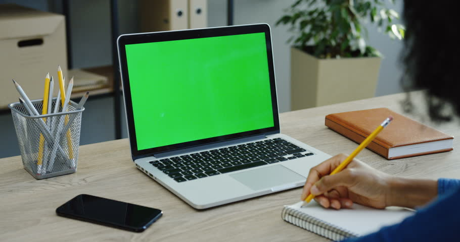 Close up of the male hands writing in the notebook with a pencil near the laptop computer with a green screen and smartphone in the office. Chroma key | Shutterstock HD Video #33502888