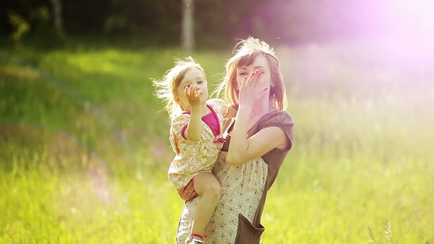 Sunny mother and child waving his hand in the park. Lens flares