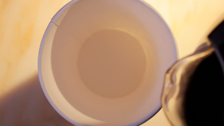 close up HD video of coffee and milk pouring into paper cup, hand takes cup away