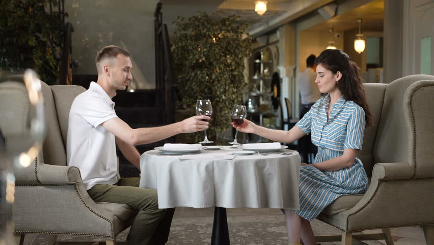 KAZAN, TATARSTAN/RUSSIA - OCTOBER 25 2017: Happy beautiful woman and man lifts up high glasses and taste red wine in modern restaurant on October 25 in Kazan | Shutterstock HD Video #33801235