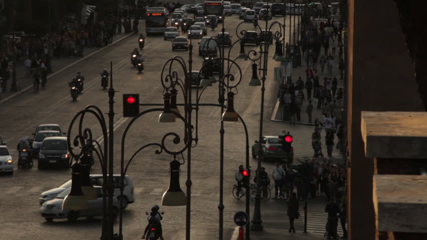 Cars, mopeds, and pedestrians travel a busy street in Rome as the sun sets.