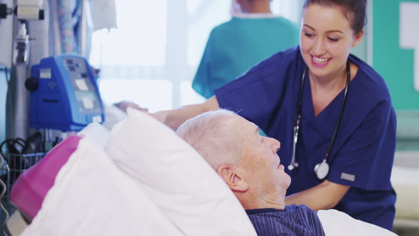 A Beautiful Female Nurse Attends To An Elderly Male Patient, Plumping Up His Pillows -3982