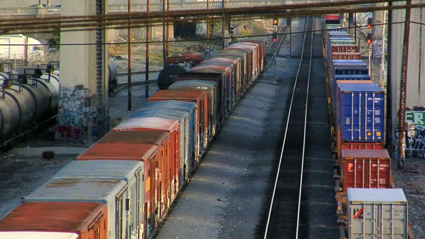 A train runs through a seedy train yard next to the Los Angeles river.  Very