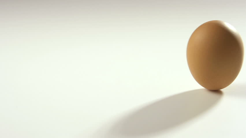 Brown egg rolling in slow motion on white table, 250 fps.