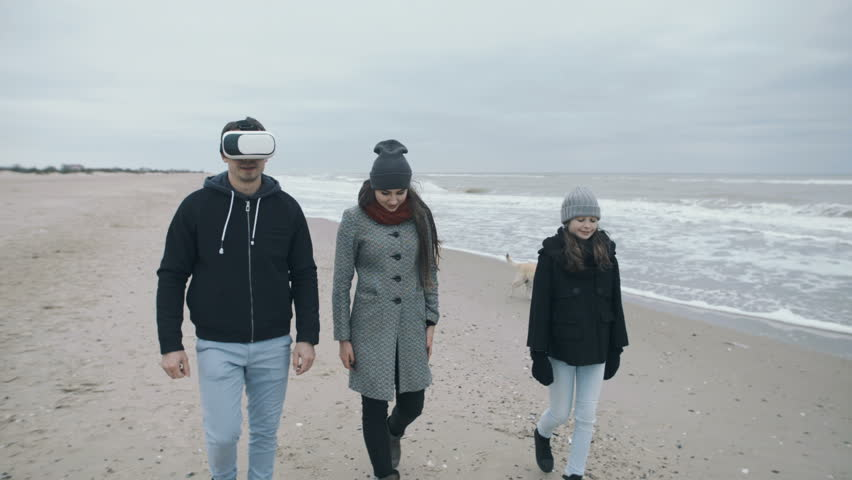 Family of the 21st century walks along the beach. The father in VR glasses.