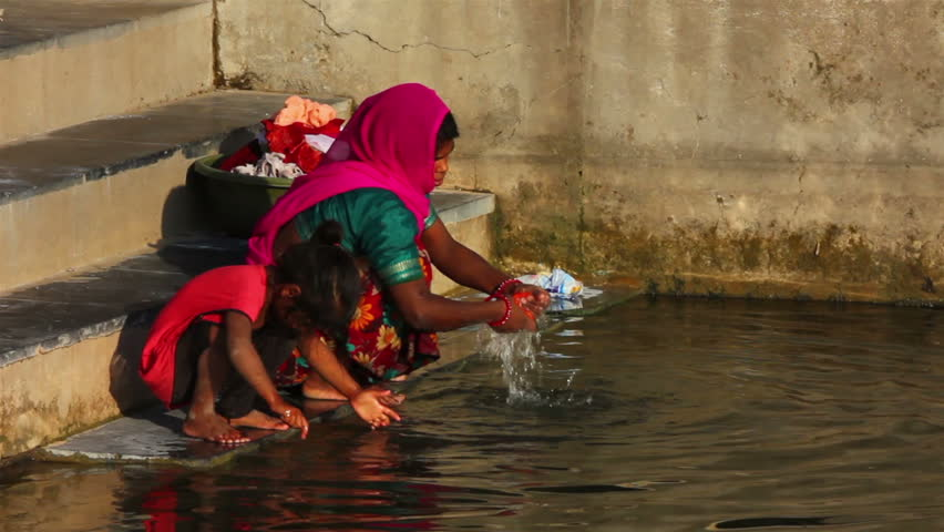 UDAIPUR, INDIA - NOVEMBER 24, 2012: Indian woman washing clothes in the lake in