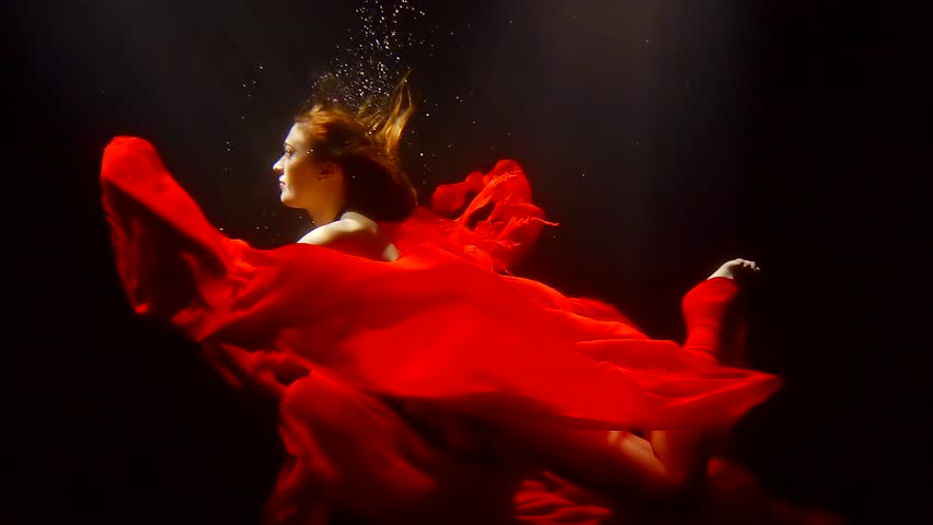 mystical redhead undine is floating underwater with red fabric around in dark deepness of river