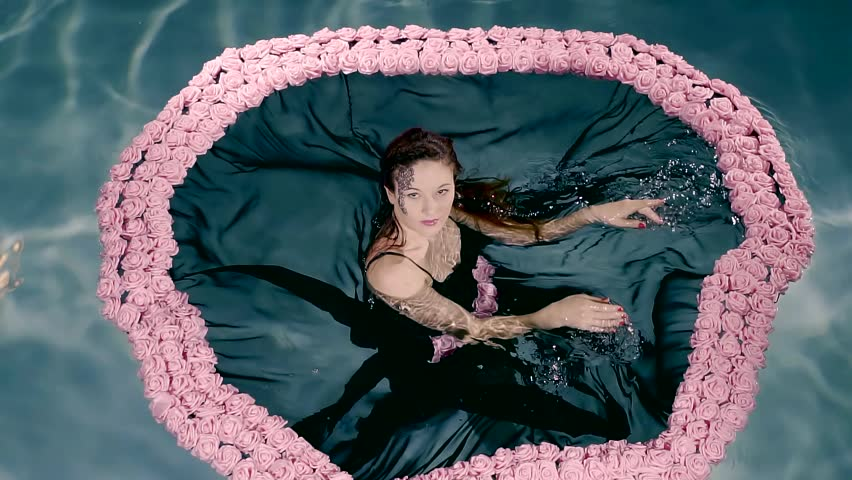 young female model is wearing black lace dress with pink roses is standing in a pool and posing