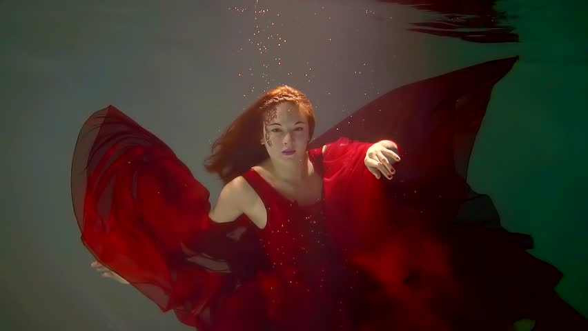 redhead girl is wearing long red chiffon dress is dancing underwater in clear pool, moving hands