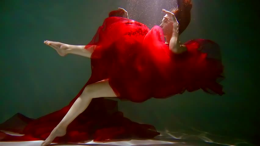 redhead girl id red long dress is falling in a pool and submerging to bottom, underwater slow mo