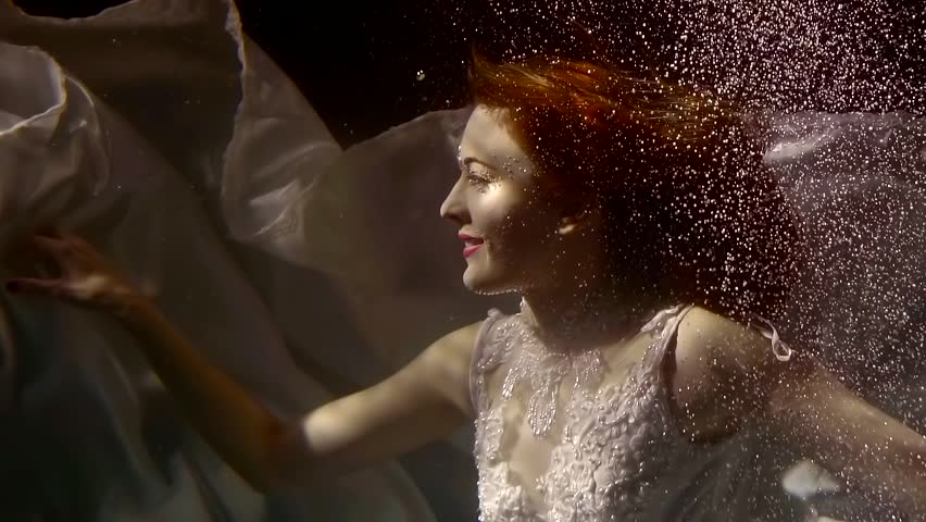 young redhead woman is in white bridal dress floating under water in sea deepness, looking on a sun