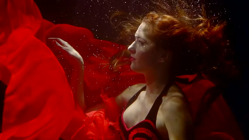 pretty elegant redhead woman is in a water in a deepness, her red dress is floating around, fairy nymph