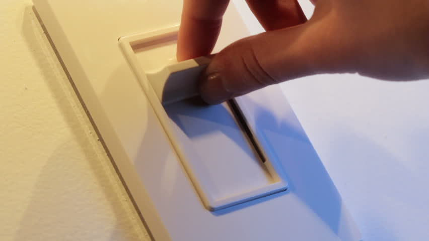 Close up of woman's hand comes into frame, turns on dimmer switch and adjusts to
