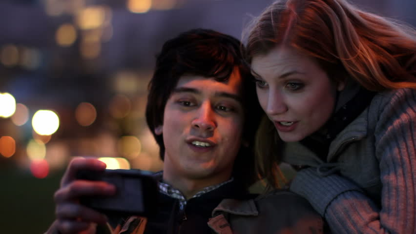Smart Phone Couple at Night.  Attractive young couple laugh as they find content on a smart phone which illuminates their faces as day turns to night.