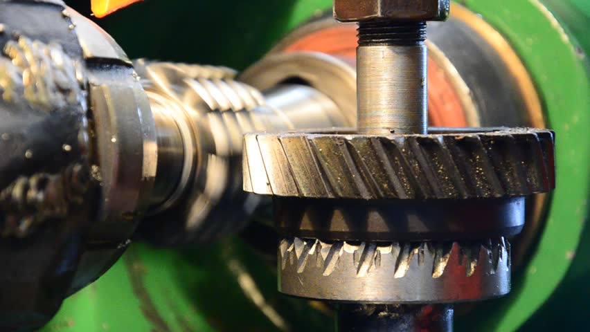 cogwheel production and service industrial machine, rotating gears closeup view
