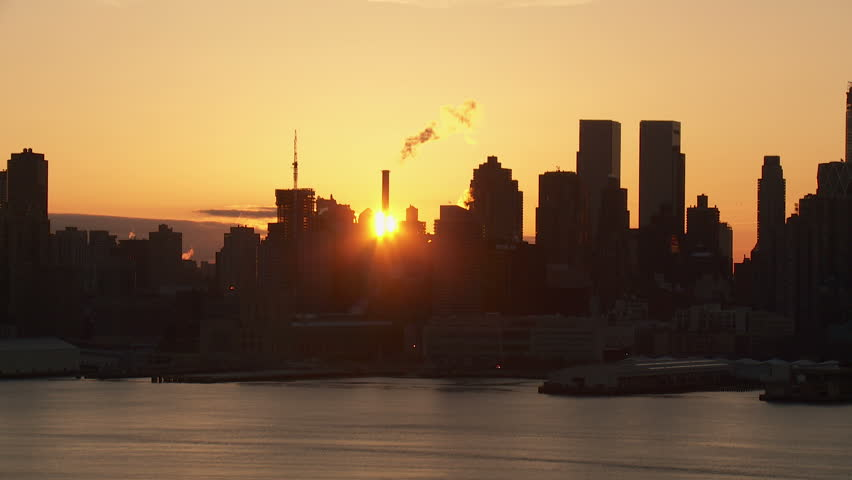 The sun rises behind the buildings of the Manhattan skyline of New York City in a timelapse sequence as viewed over the Hudson River looking east from New Jersey. | Shutterstock HD Video #3568913