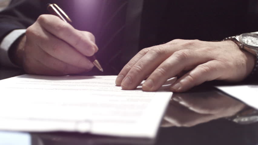 Businessman sitting at shiny office desk signing a contract with noble pen   Shutterstock Video #3582926