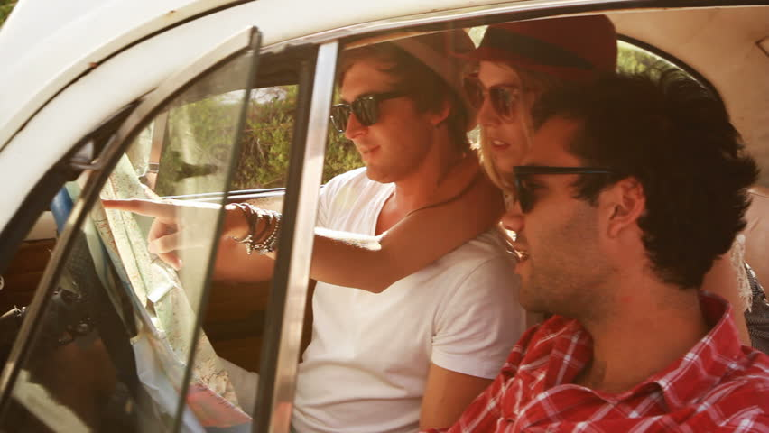 Young Hipster friends on a roadtrip looking at a map.   Shutterstock Video #3591233