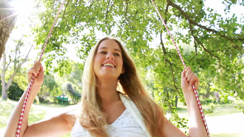 Young beautiful woman is having fun on a swing underneath a tree in nature.