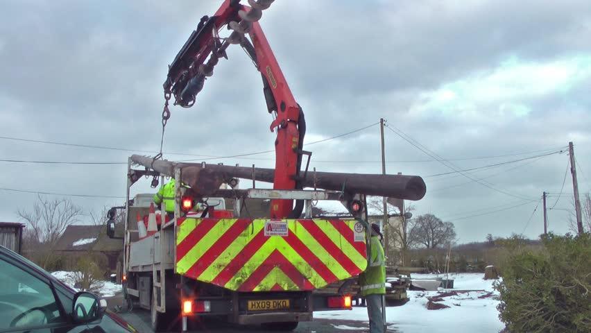 Truck Unloading Telegraph Poles