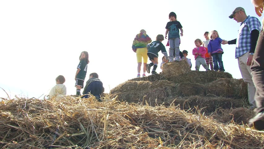 PORTLAND, OREGON - CIRCA 2012: Kids playing on haystacks jump off and laugh on