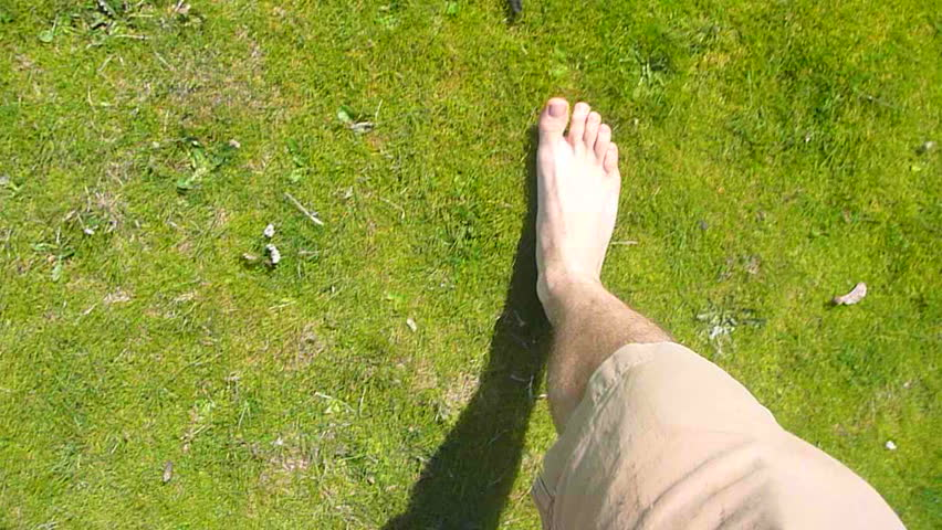 Point of view of man walking barefoot through grass field.