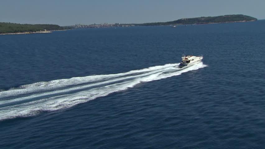 A speedboat speeds across Adriatic sea near islands. Aerial helicopter shot.