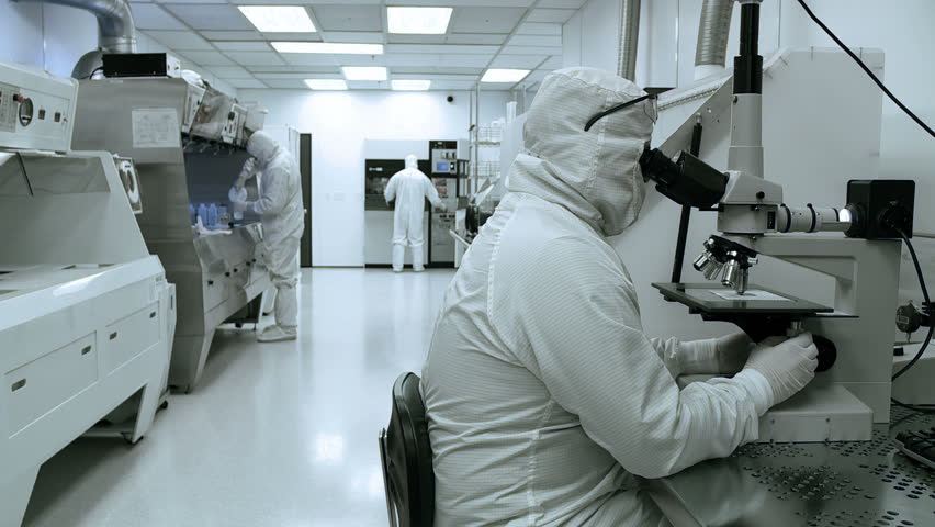Scientists and technicians working on silicon chip manufacture in a clean room,