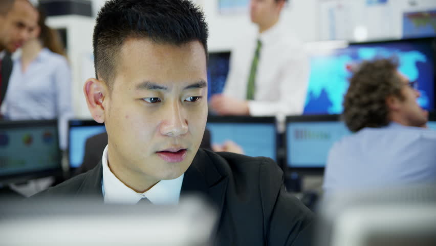 Young and ambitious stock market trader is doing a deal over the phone in a busy office filled with computers. The rest of his team are hard at work in the background.  | Shutterstock HD Video #3673124