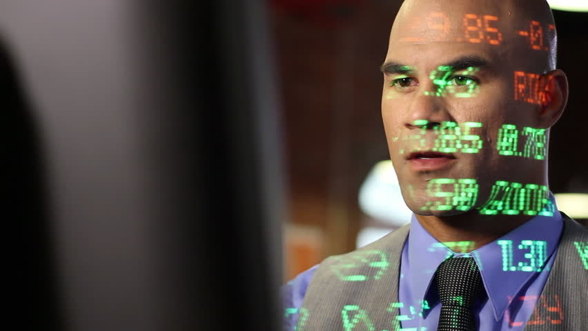 City trader watches his computer screen with a look of confidence as various