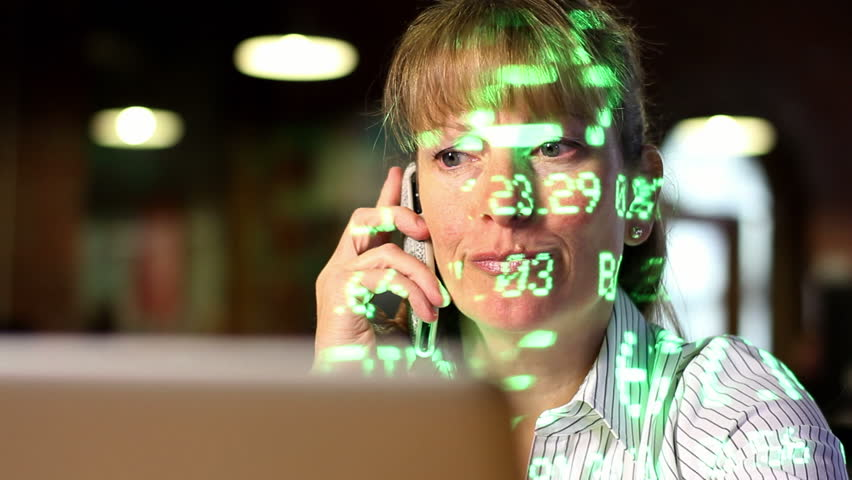 Woman making trades on the stock market with a laptop and a phone. Stock ticker