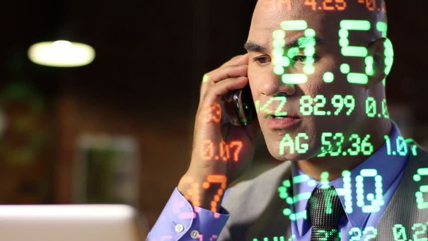 City guy making deals on the phone while ticker symbols of varying size are