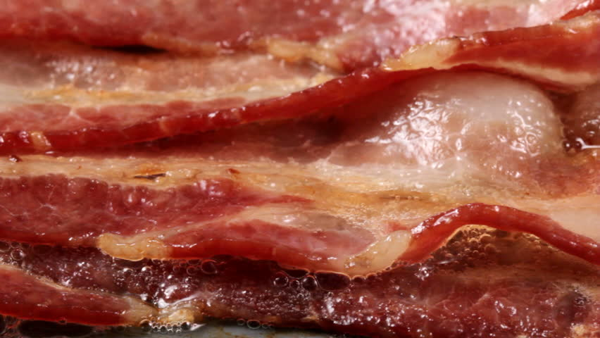 Extreme closeup pan of bacon cooking on a griddle