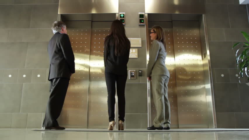 Business people wait for an elevator, get in when it arrives. Wide view,