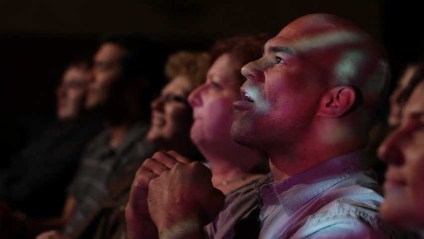 Young man has various reactions while watching a movie with a group of friends.