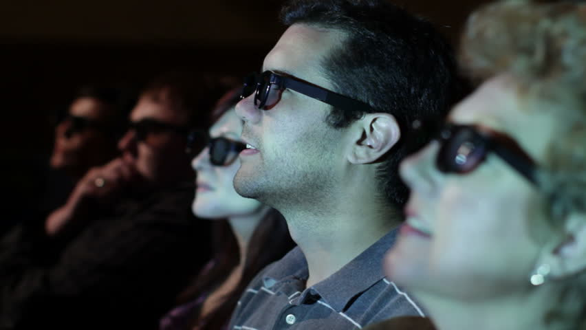 Young man watching a 3D movie with a group of friends. Focus on him with a small