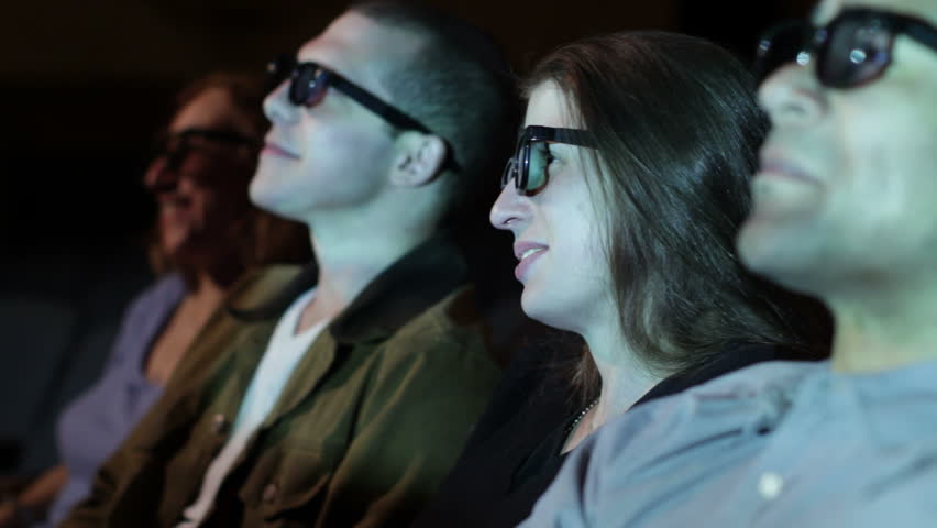 Young woman applauds as she watches a 3D movie. Focus on her with a small dolly