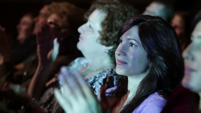 Attractive young woman applauds a movie. Focus on her with a small dolly move