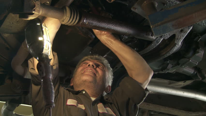Auto mechanic working on the underside of a car. Hand held shot.