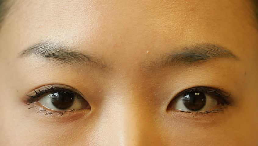 beautiful young woman opens her blue eyes closeup
