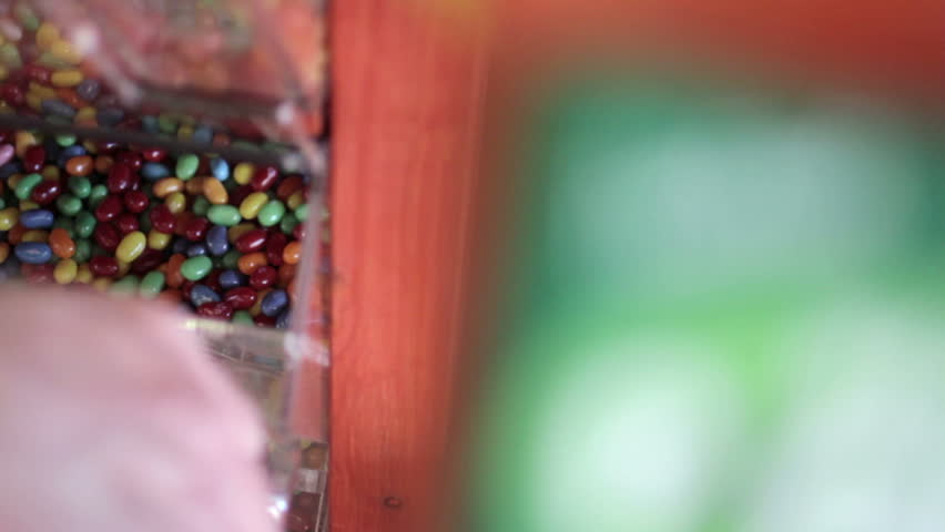 Detail of jelly beans being scooped from a selection in a candy store and into a