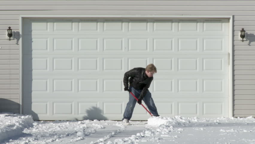 Young man digs away snow from in front of a garage in the Mid West, USA. Wide