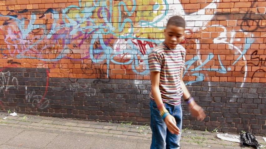 Street Dance - Mixed race boy street dancing in urban setting
